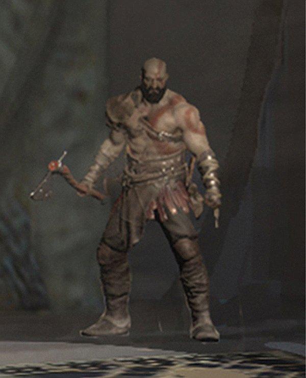 Kratos aparece segurando um machado e com uma longa barba negra,